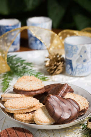 Some cookies, small fir branch , pine cones,  candles and Christmas ornaments are set on holiday napkin and ready for family time. photo