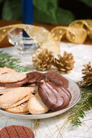 Some cookies, small fir branch , pine cones,  blue candle and Christmas ornaments are set on holiday napkin and ready for family time. photo