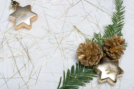 Small fir branch, golden cones amd ornament stars on spangled holiday napkin