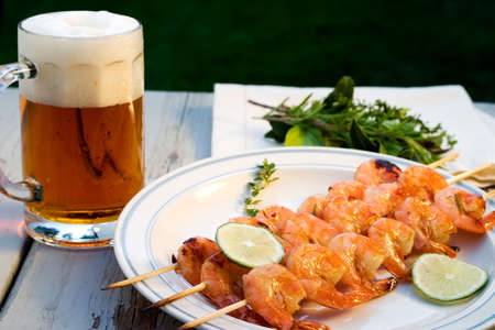 Grilled shrimps on wood sticks served with lime and mug of pale ale