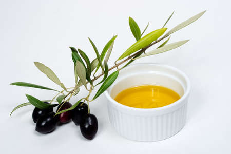 Extra-virgin olive oil and black olives branch on white paper Stock Photo