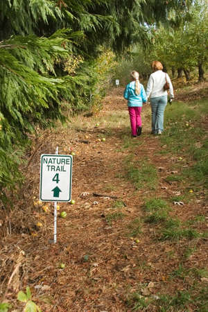 Mother with daughter are having healthy time outside in fall on the nature trail in middle of apples garden photo