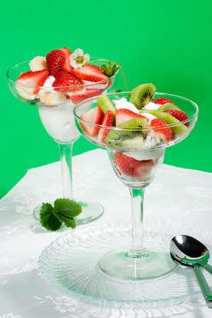 strawberies: Martini glass full of fresh kiwi, strawberies and cream with organic yogurt Stock Photo
