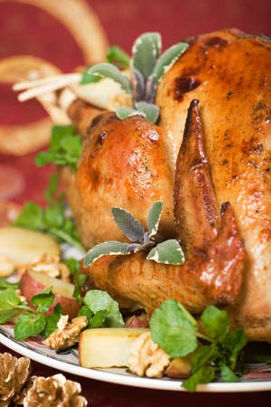 Christmas turkey served with herbs, baked potatos and walnuts on holliday table