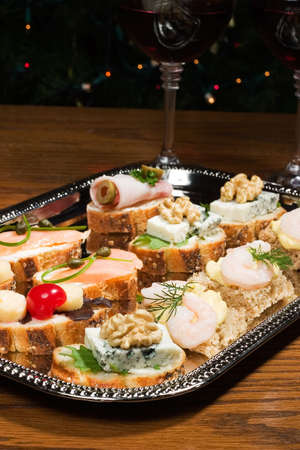 Tray with sandwiches on holiday table with wine and Christmas tree with lights on background photo