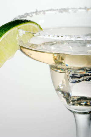 Martini glass full of cocktail with ice over white paper background served with lime Stock Photo - 671425