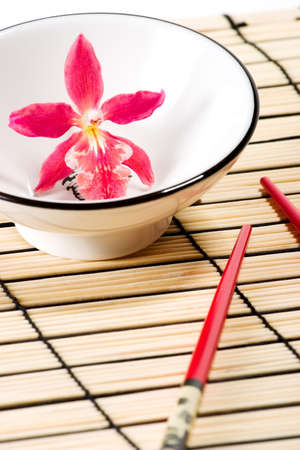 Sushi set on bamboo  place mat  and red orchids flower in empty bowl photo