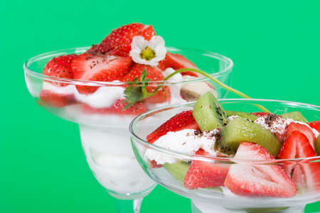 Closeup of martini glass full of fresh kiwi, strawberries, banans and cream with organic yogurt sprinkled by chocolate crumbles over green paper background photo