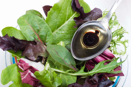 balsamic: Closeup of plate full of organic spring mix salad and spoon of natural olive oil with Balsamic vinegar over it Stock Photo