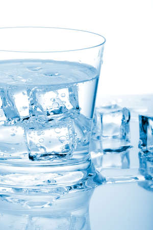 Glass of fresh water with cubes of ice in it over paper background Stock Photo