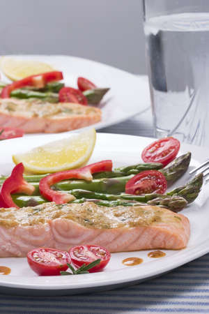Rosemary roasted salmon served with asparagus, cherry tomatoes, red bell pepper topped by mustard rosemary sauce and glass of ice water for healthy style dinner photo