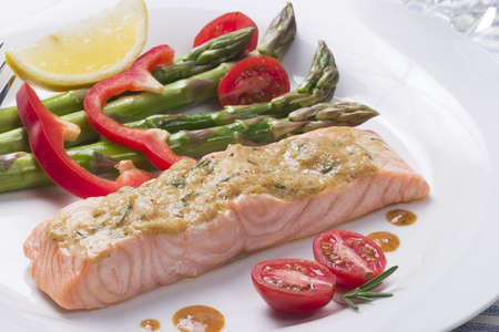 Rosemary roasted salmon served with asparagus, cherry tomatoes, red bell pepper topped by mustard rosemary sauce and slice of lemon for healthy style dinner photo