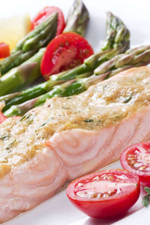Closeup of rosemary roasted salmon served with asparagus, cherry tomatoes, red bell pepper topped by mustard rosemary sauce for healthy style dinner photo