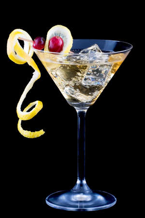 Closeup of martini glasses with lemon and cranberry splash cocktail over black background