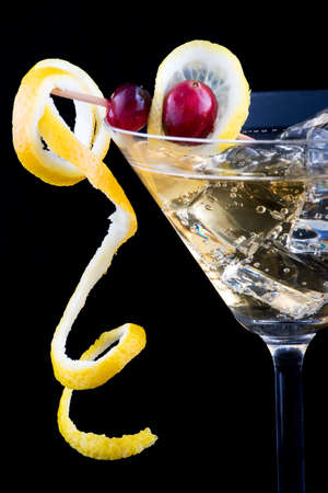 Closeup of martini glasses with lemon and cranberry splash cocktail over black background photo