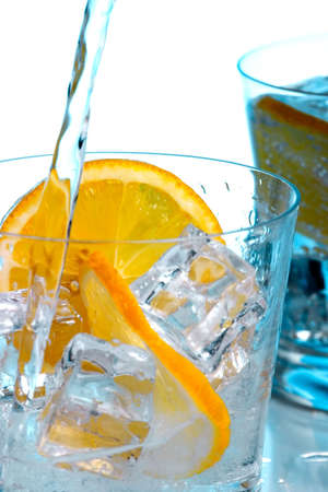 Pouring fresh water into one of two glasses with water, sliced lemon and ice cubes over aqua paper background photo