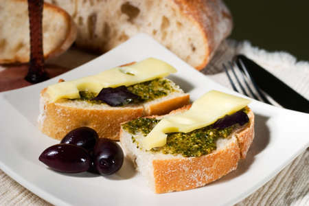 Organic ciabatta bread with pesto dressing and black olives photo