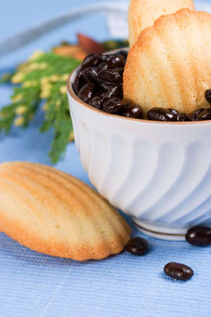 Petite French cakes Madeleines inside a porcelain cup full of coffee beans in Christmas decoration on blue napkin Stock Photo - 759775
