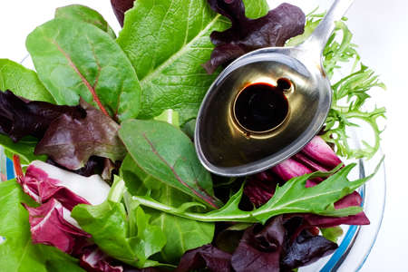 lettuces: Closeup of plate full of organic spring mix salad and spoon of natural olive oil with Balsamic vinegar over it Stock Photo