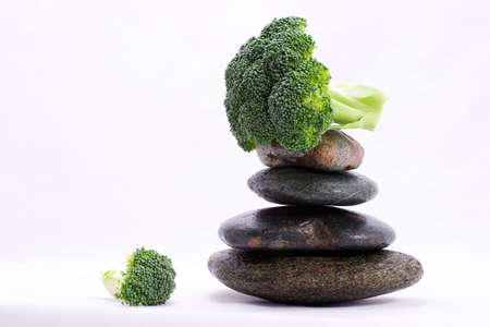 Peace of broccoli on the top of zen stones pyramid in balance photo