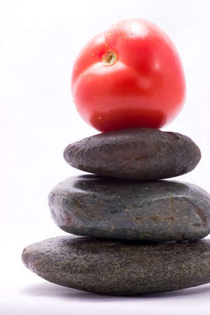 Closeup of tomato on the top of zen stones pyramid in balance photo