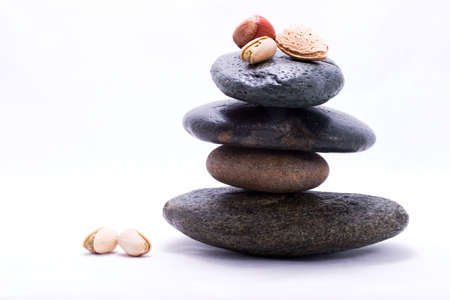 Three types of nuts on the top of zen stones pyramid in balance. Almonds, pistachio and filbert in the shells. photo