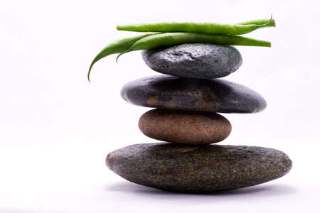 Three pods of green beans on the top of zen stones pyramid in balance photo
