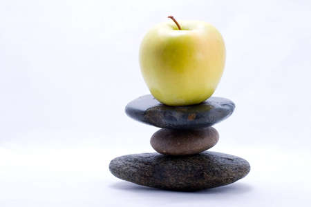 Apple on the top of zen stones pyramid in balance photo