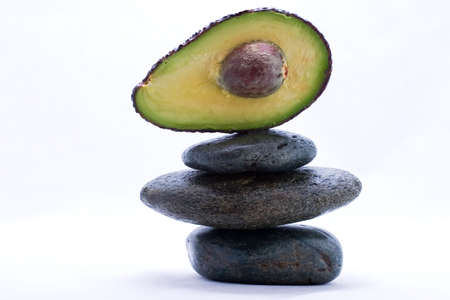 Half cut avocado on the top of zen stones pyramid in balance photo