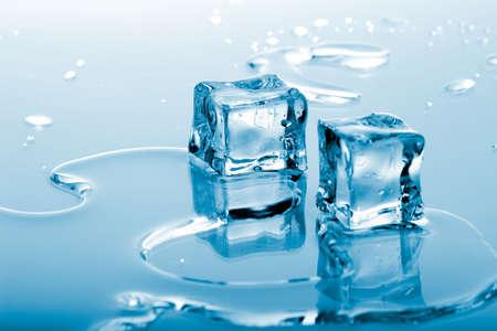 melting: Dos cubitos de hielo de color azul en el agua derretida en la superficie de reflexi�n listo para ser a�adido a un c�ctel  Foto de archivo