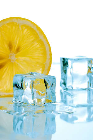 Two ice cubes melted in water and slice of lemon on reflection surface ready to be added to a cocktail