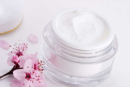 Closeup of open container of moisturizing face cream and blooming twig of plum on white background with small pink petals around  Stock Photo - 803602