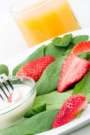 Close up of spring mix organic spinach and strawberries salad with yogurt deep and glass of orange juice over white background photo