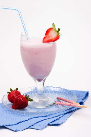 Strawberry milkshake, strawberries and cookes on glass plate on blue napkin over white paper background. photo