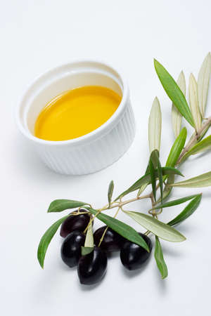 Extra-virgin olive oil and black olives branch on white background