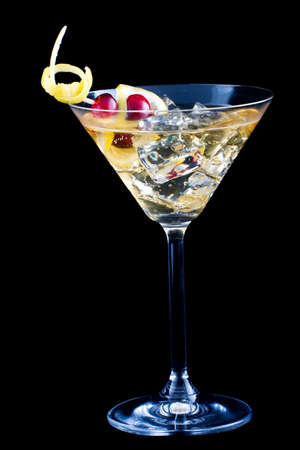 Closeup of martini glass with lemon and cranberry splash cocktail over black background