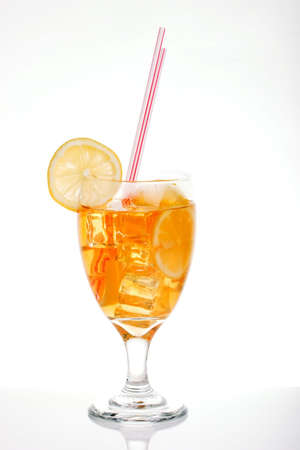 tall glass: Single tall glass of iced tea full of ice cubes, slices of lemon and two straws over white background