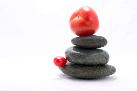 Tomato on the top of zen stones pyramid in balance photo