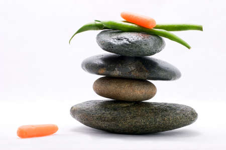 Pods of green beans and  carrot on the top of zen stones pyramid in balance Stock Photo