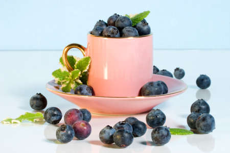 Pink coffee cup over aqua paper background full of blueberries and mint leaves photo
