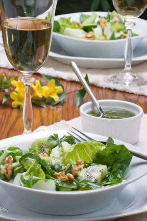 Sharp and sweet green organic salad with walnut. lime-pepper dressing and glass of white wine for dinner Stock Photo - 837819