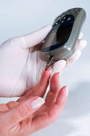 Nurse is doing glucose level finger blood test