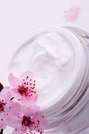 cremas faciales: Extrema de cerca de abrir el recipiente de la crema facial hidratante y florece ramita de ciruela