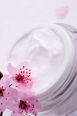 Extreme closeup of open container of moisturizing face cream and blooming twig of plum Stock Photo - 848773