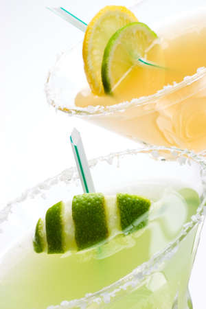 wedges: Closeup of Golden Margarita and Midori Margarita tequila cocktails garnished with lime and lemon wedges Stock Photo