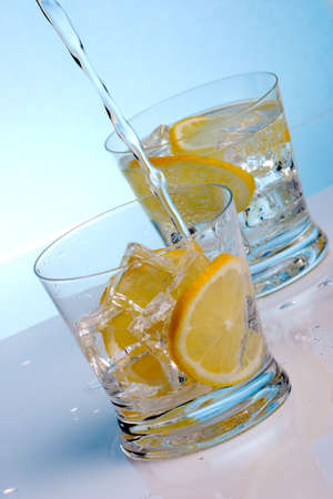 Pouring fresh water into one of two glasses with cocktails, sliced lemon and ice cubes over aqua paper background photo