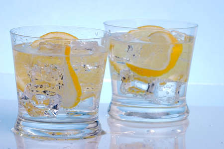 Two glasses with cocktails, sliced lemon and ice cubes over aqua background photo