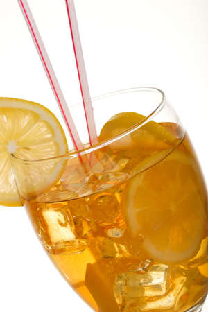 Single tall glass of iced tea full of ice cubes, slices of lemon and two straws over white background