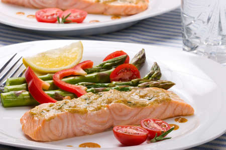 glass topped: Rosemary roasted salmon served with asparagus, cherry tomatoes, red bell pepper topped by mustard rosemary sauce and glass of ice water for healthy style dinner