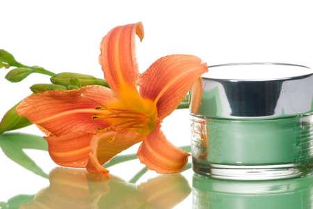 cremas faciales: Primer del envase de la crema de la cara que humedece y del lirio floreciente en fondo entonado verde Foto de archivo